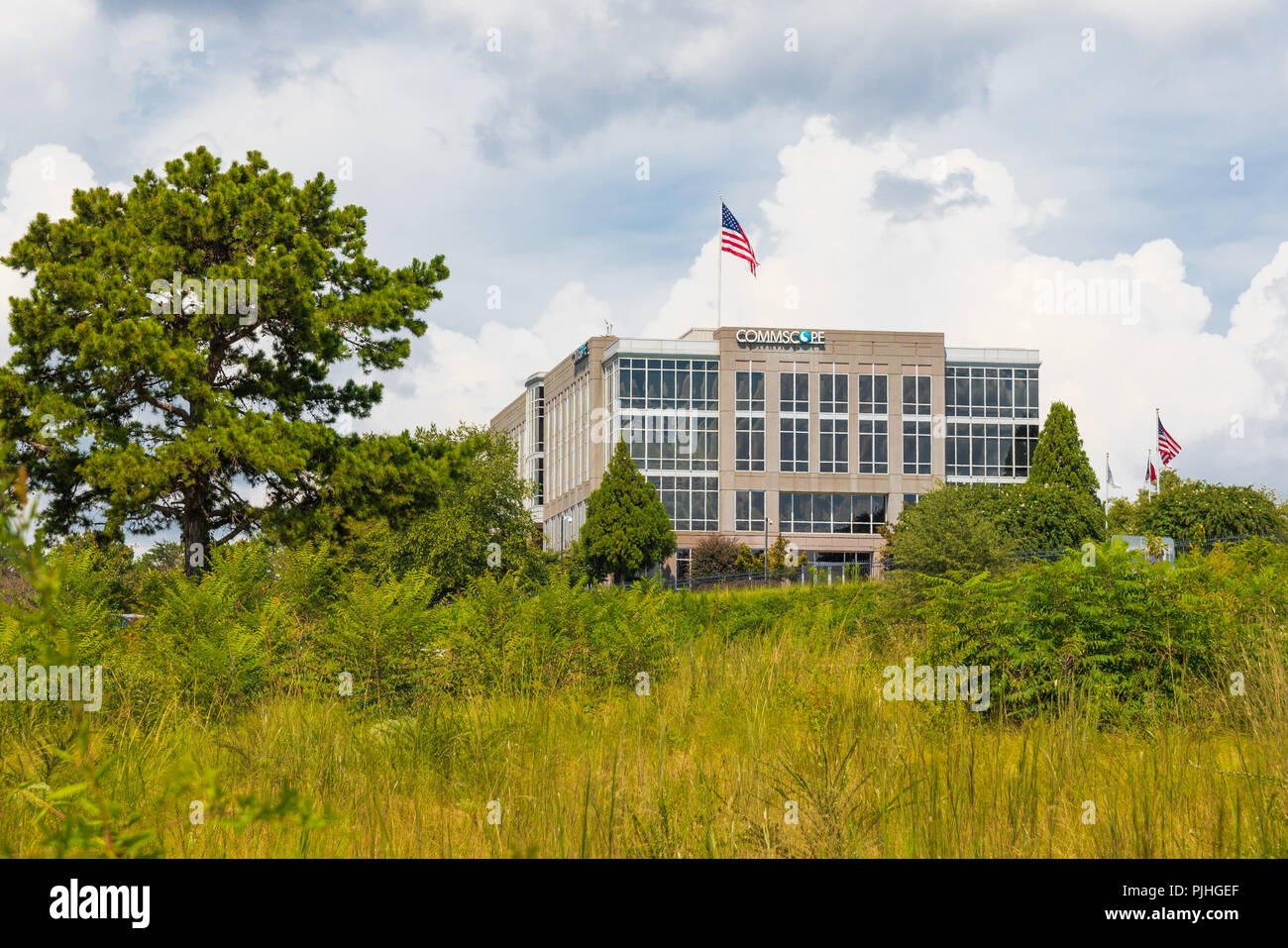 HICKORY, NC, USA-9/6/18: The Commscope corporate building, based in Hickory, stands beyond a green field with bushes and small trees. Stock Photo