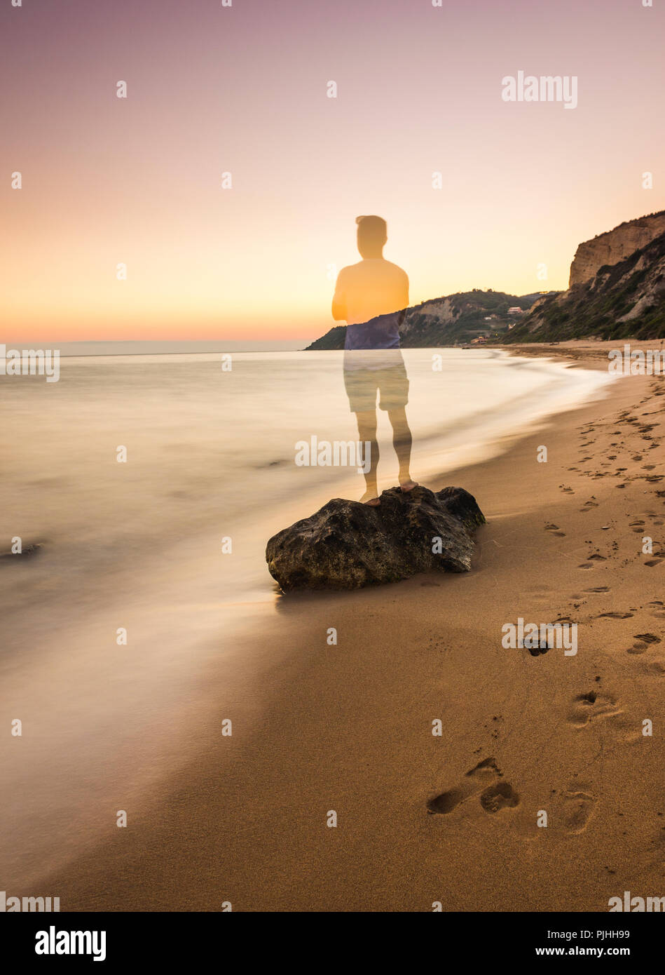 Long exposure of a person standing on a rock by the shore. Opaque effect. - Stock Image