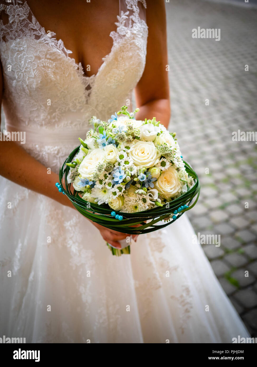 The Bride Holds The Bouquet With White Roses And Little Blue