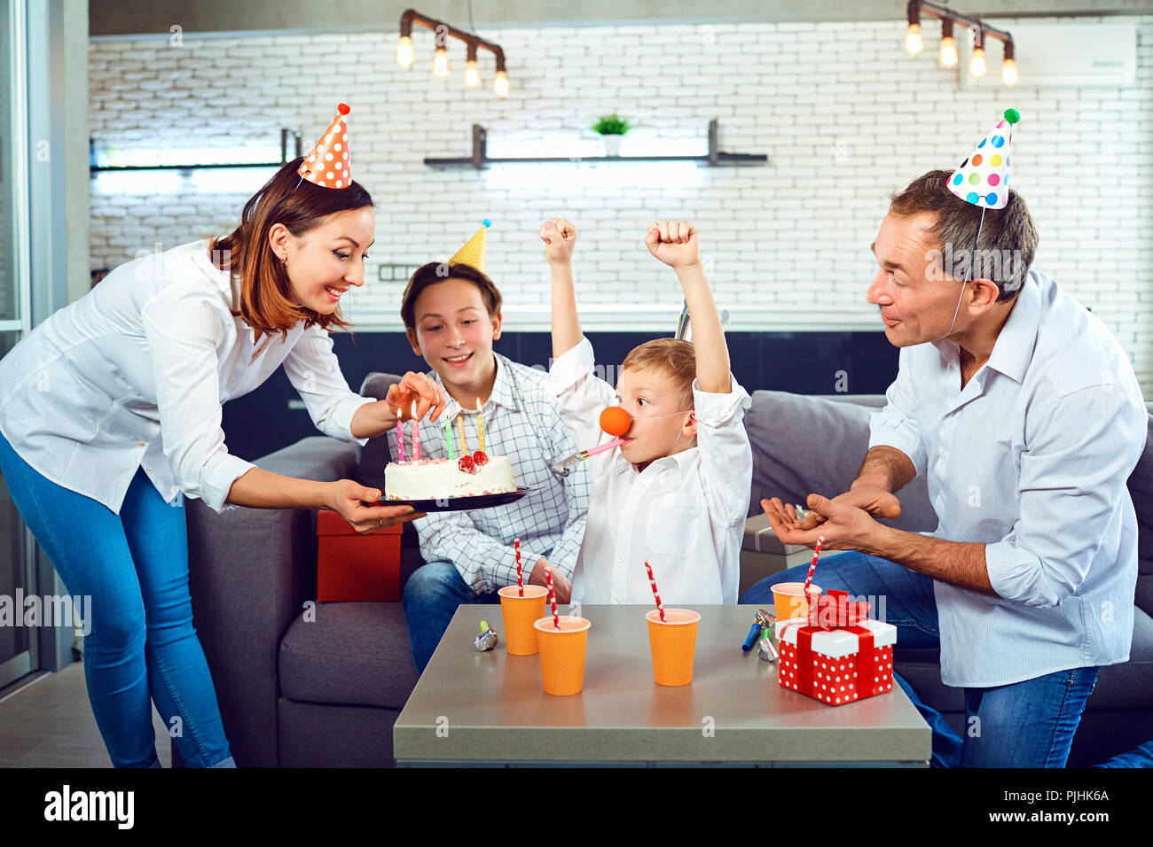 A family with a candle cake celebrates a birthday party. - Stock Image
