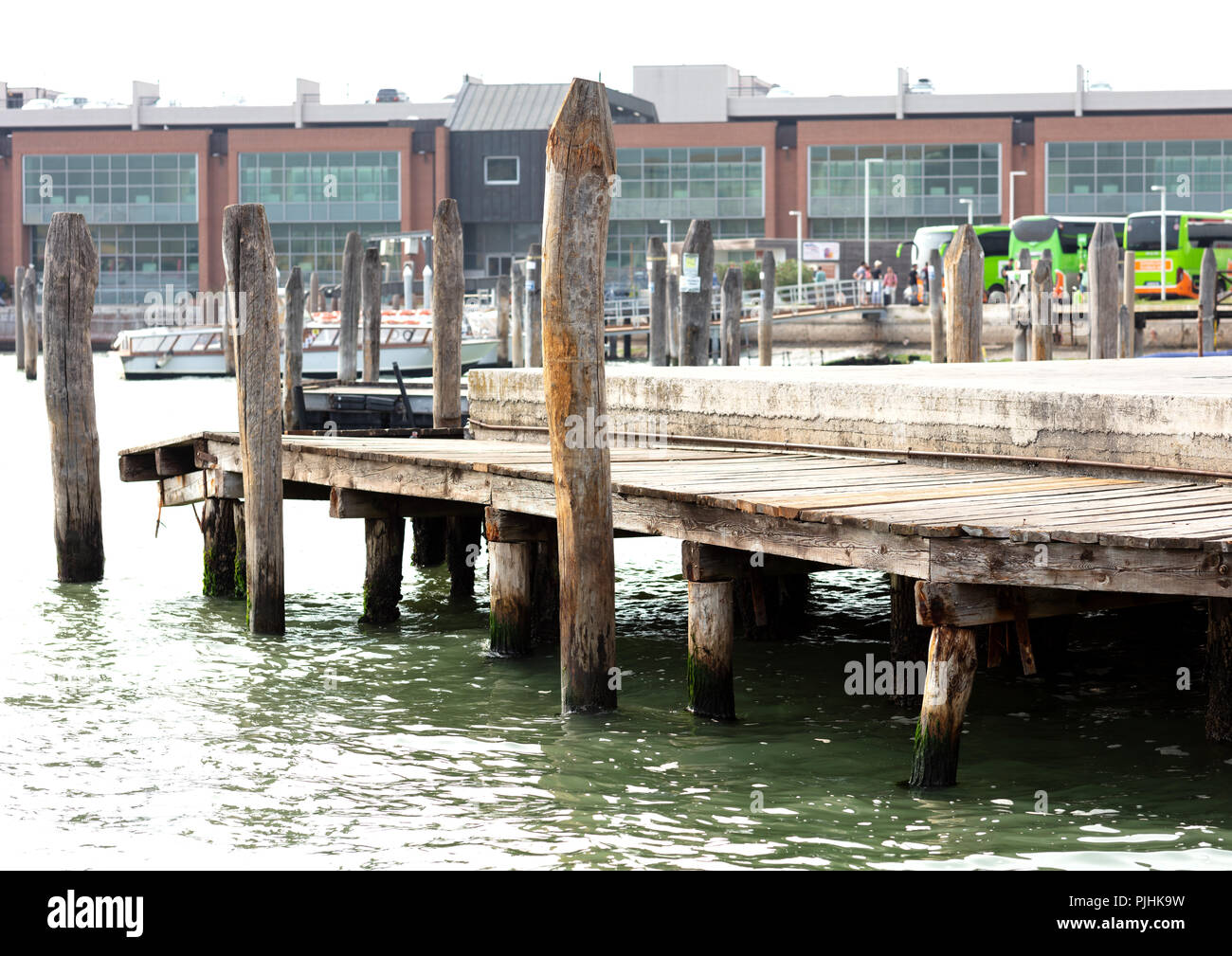 wooden pier supported in piles to embark tourist in Venice, in the background three green buses with a group of people and boats - Stock Image