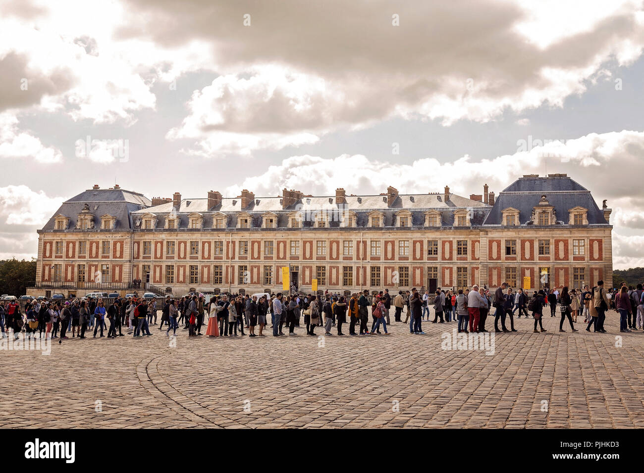 Throngs of tourists lining up to enter the famous Chateau de Versailles in Paris - Stock Image