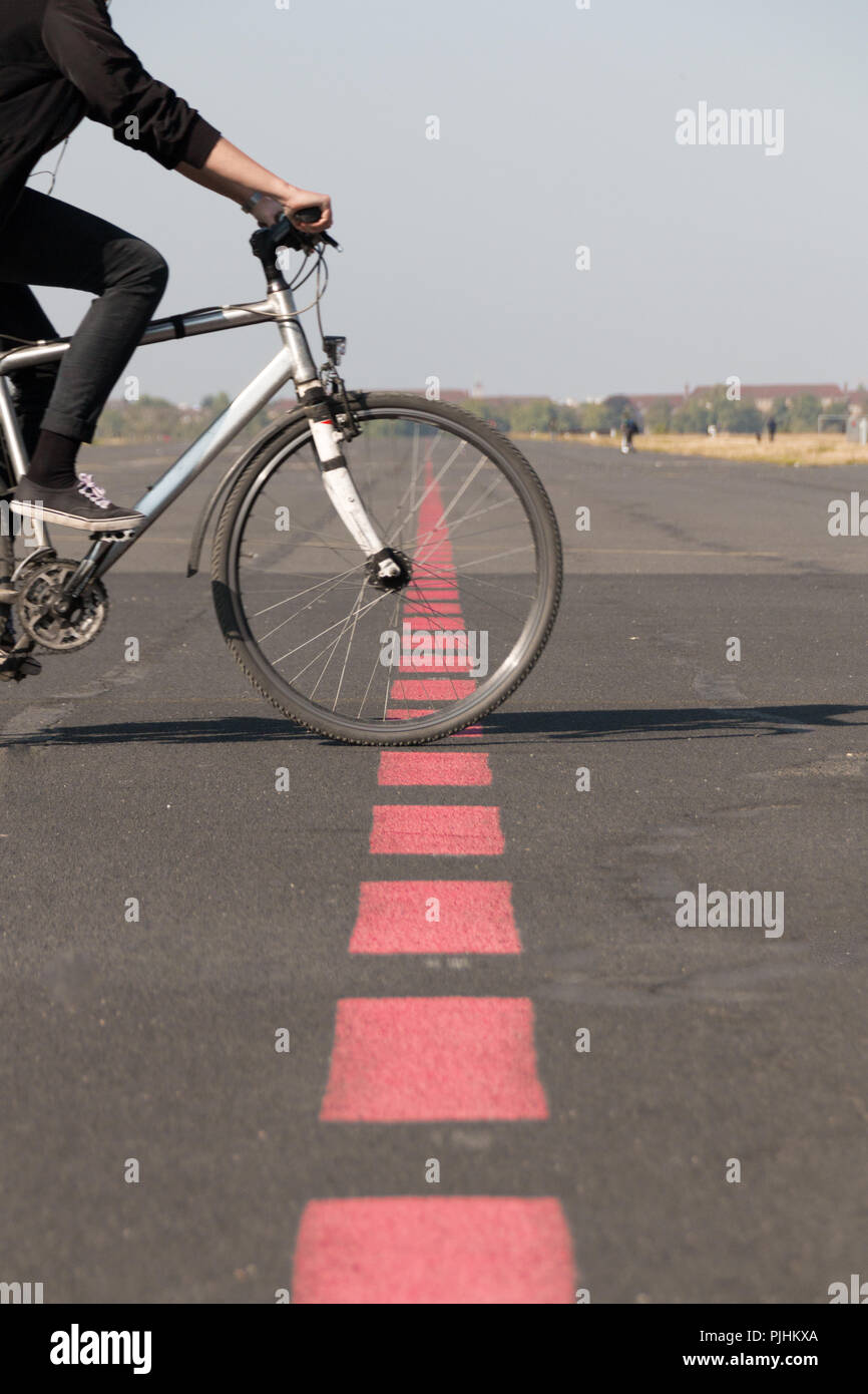 Berlin, Germany - September 6, 2018: View of the runway of the former Tempelhof Airport in Berlin which is being crossed by a cyclist, Germany. - Stock Image