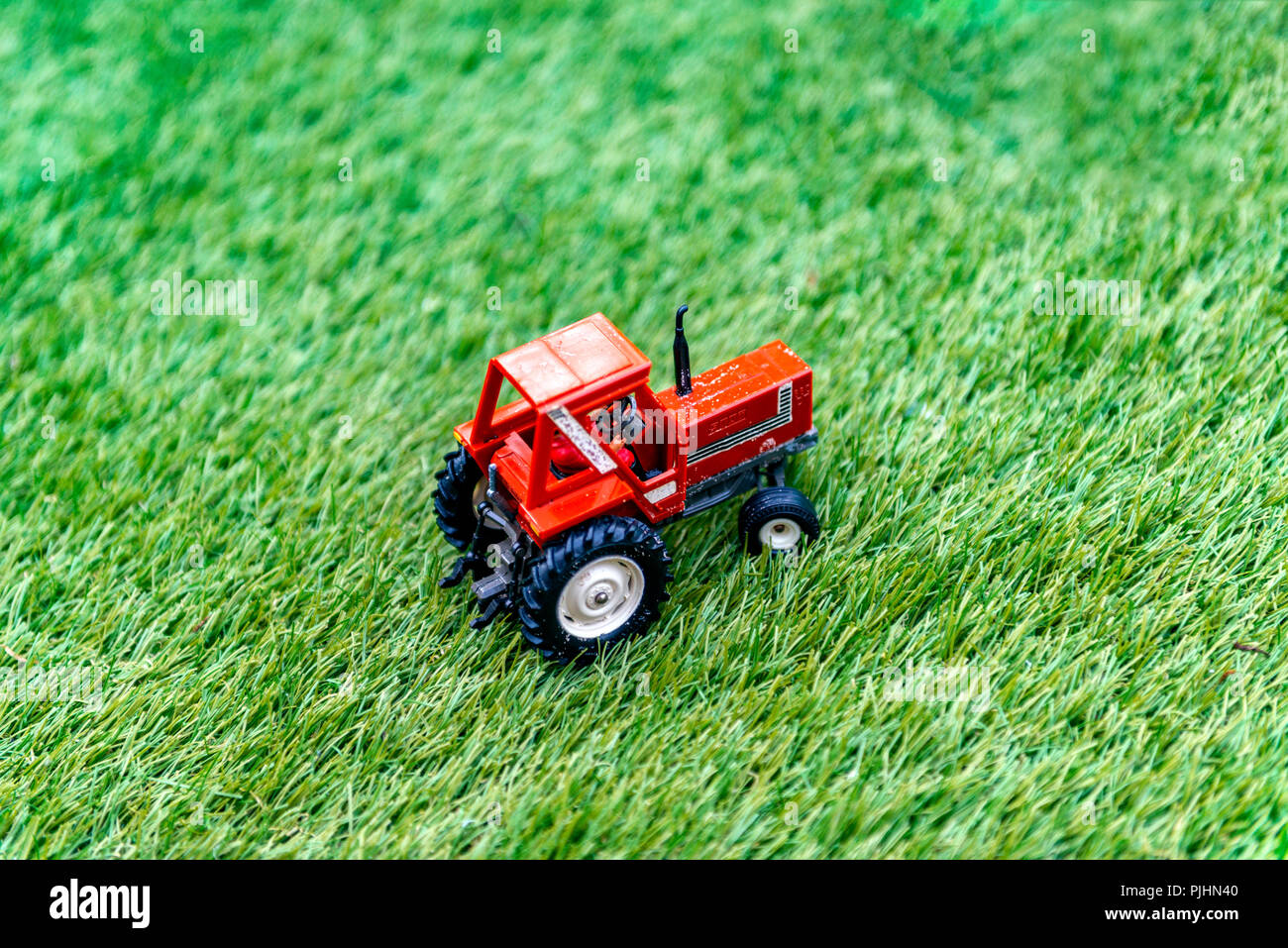 Miniature toy tractor on fake grass Stock Photo