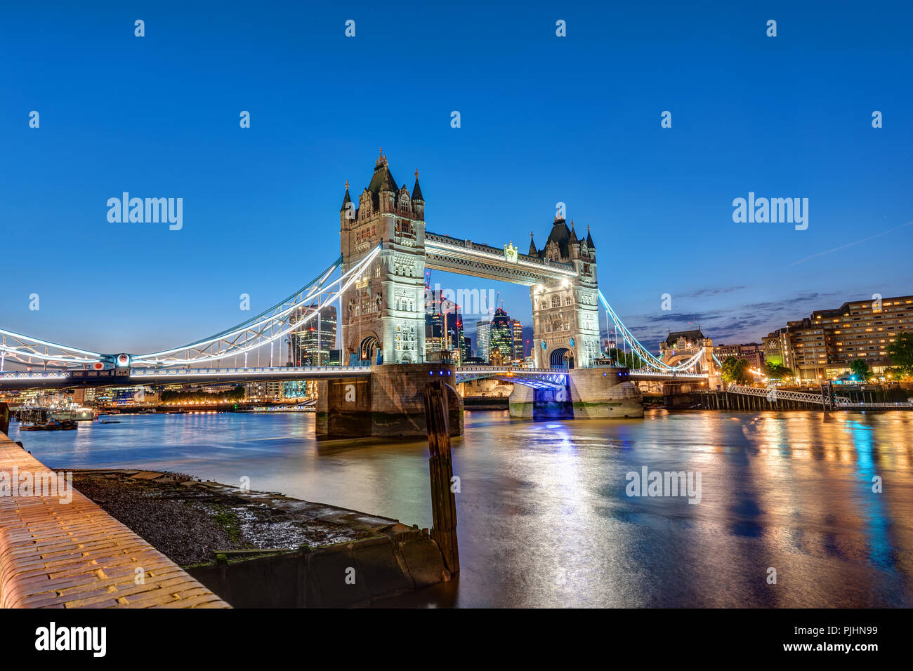 The Tower Bridge in London at night with the City in the back - Stock Image