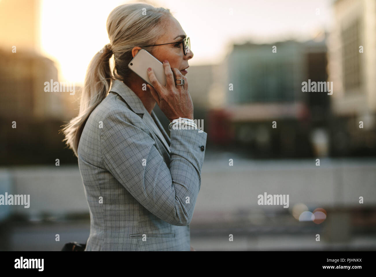 Side view of senior business professional walking outside on road talking on cell phone. Mature businesswoman walking outdoors on street with mobile p - Stock Image