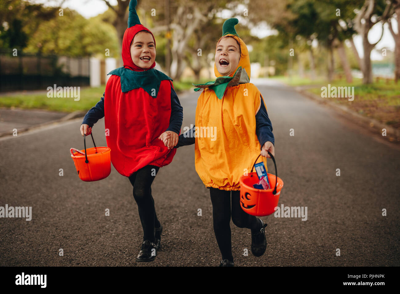 happy kids in halloween costume trick or treating outdoors two little girls in halloween costume with buckets walking outdoors on the street