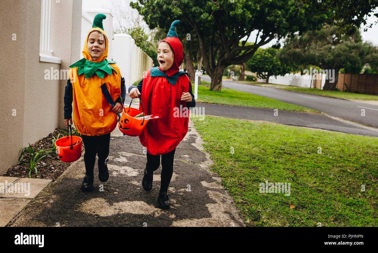 Identical twin sisters in halloween costume with halloween bucket walking on sidewalk. Halloween kids trick or treating. - Stock Image