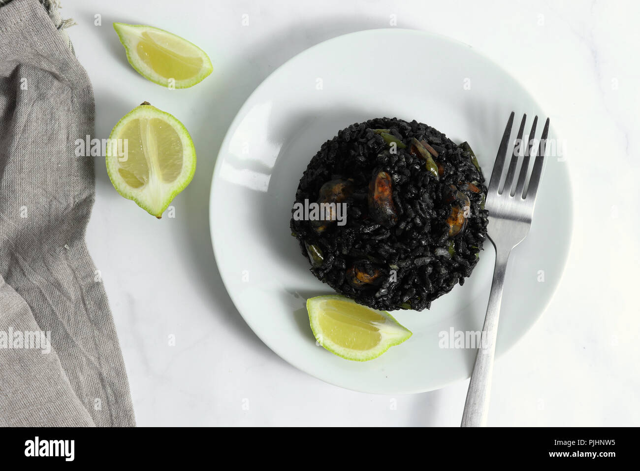 Traditional arroz negro - arròs negre - black rice dish, typical for Valencia, on white marble surface Stock Photo