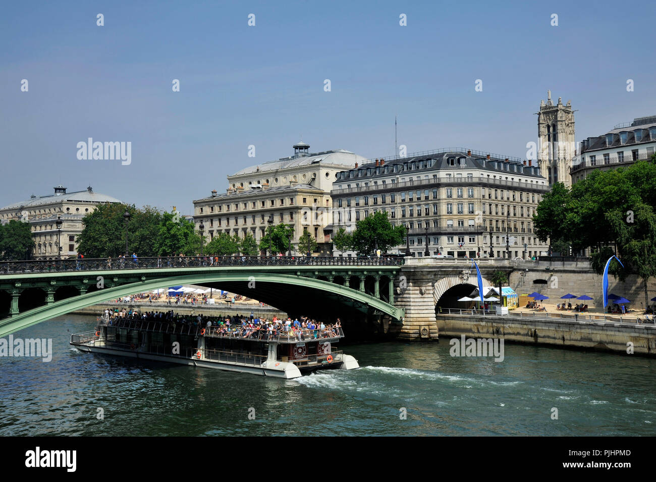 France, Paris City, riverboat carrying visitors on the Seine under the Notre-Dame bridge. - Stock Image
