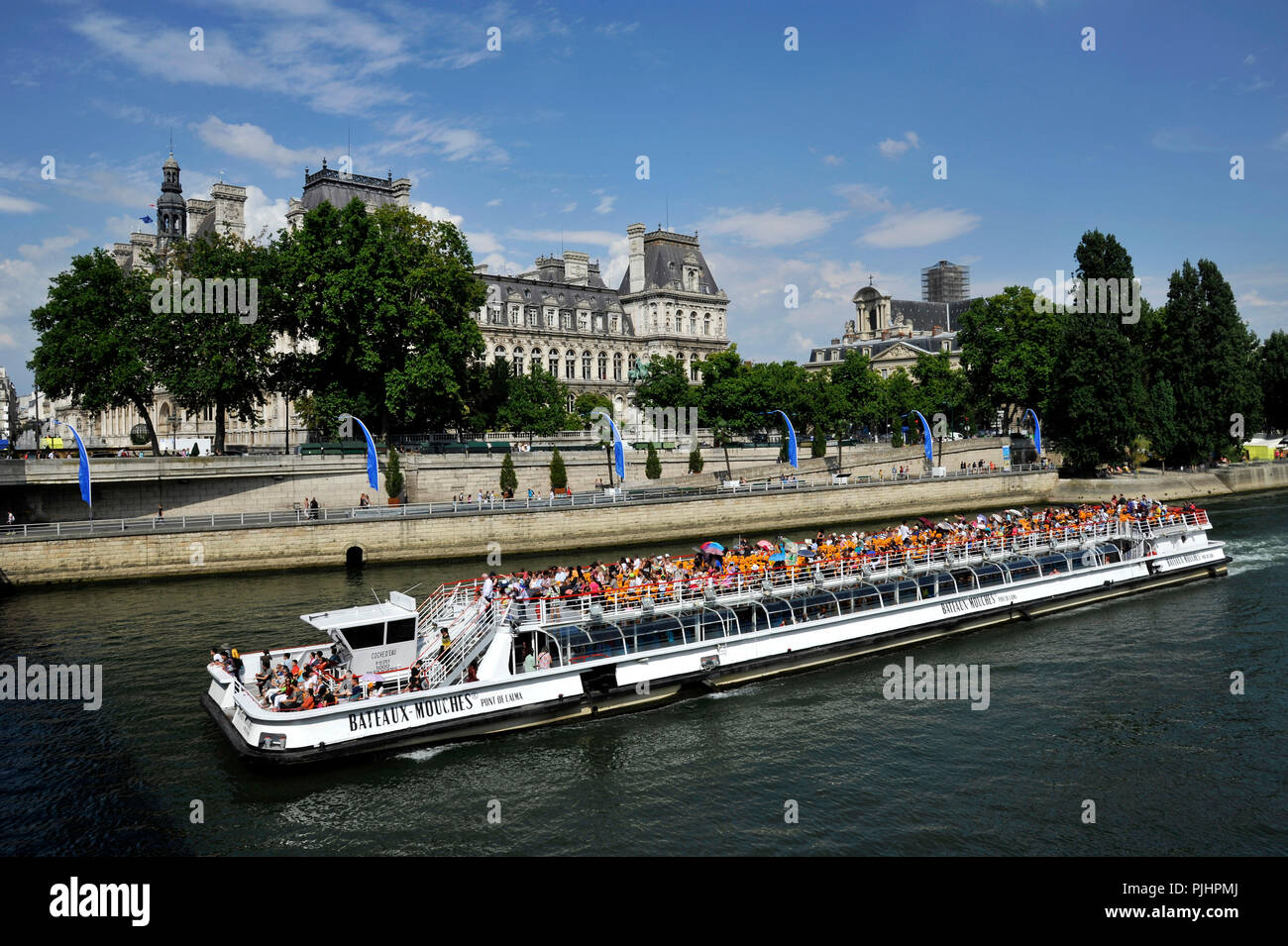 France, Paris City, riverboat carrying visitors on the Seine in front of Paris City Hall. - Stock Image
