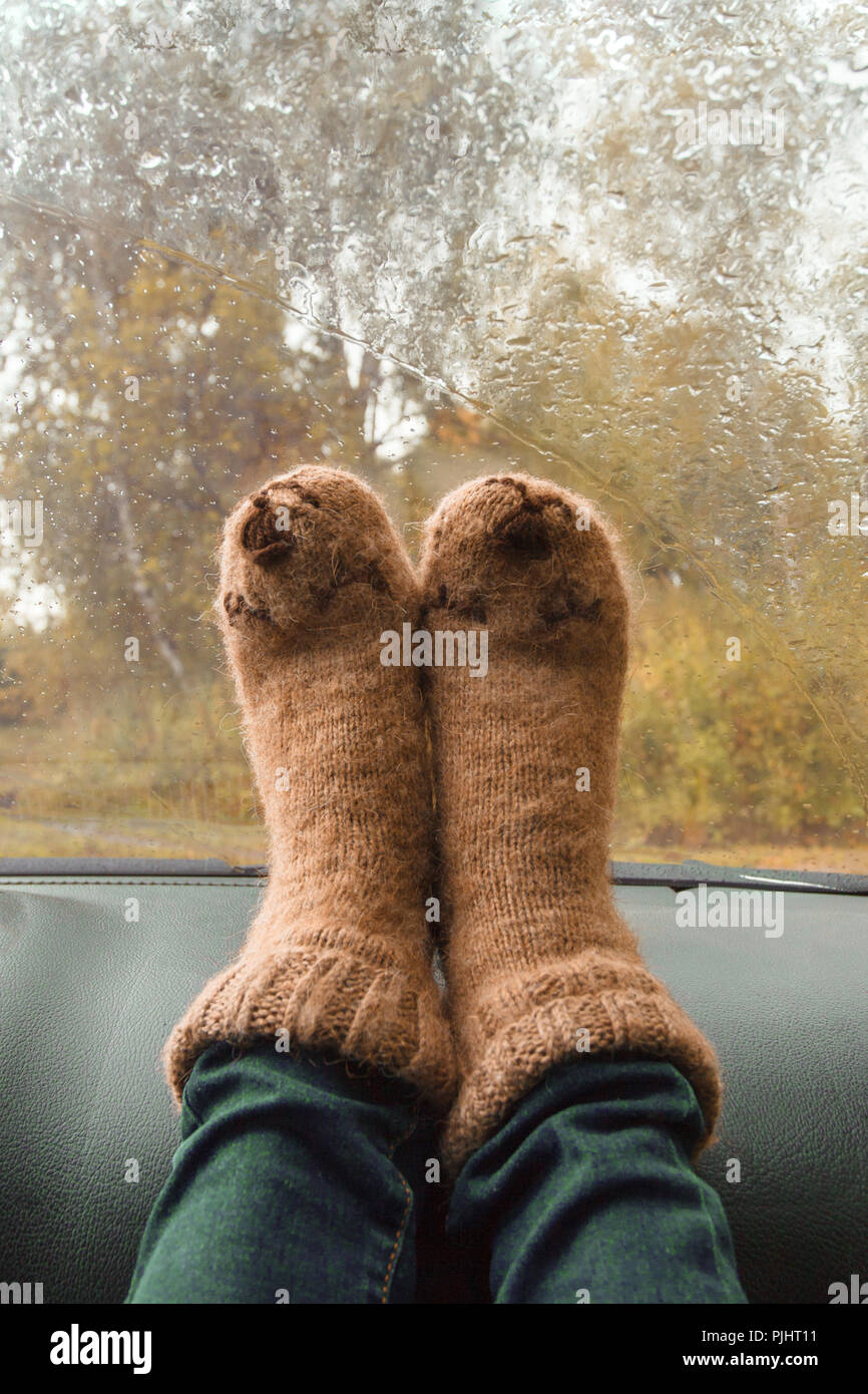 Autumn car trip. Woman feet in warm wool socks in the car. Rain drops on windshield. Freedom travel concept. Autumn weekend. - Stock Image