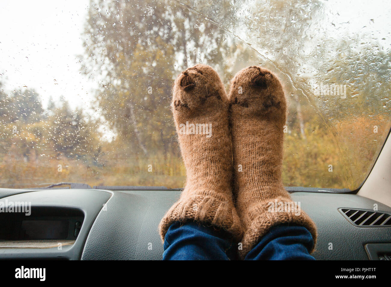 Feet in warm cute socks on car dashboard. Travel, road trip and autumn fall concept. - Stock Image