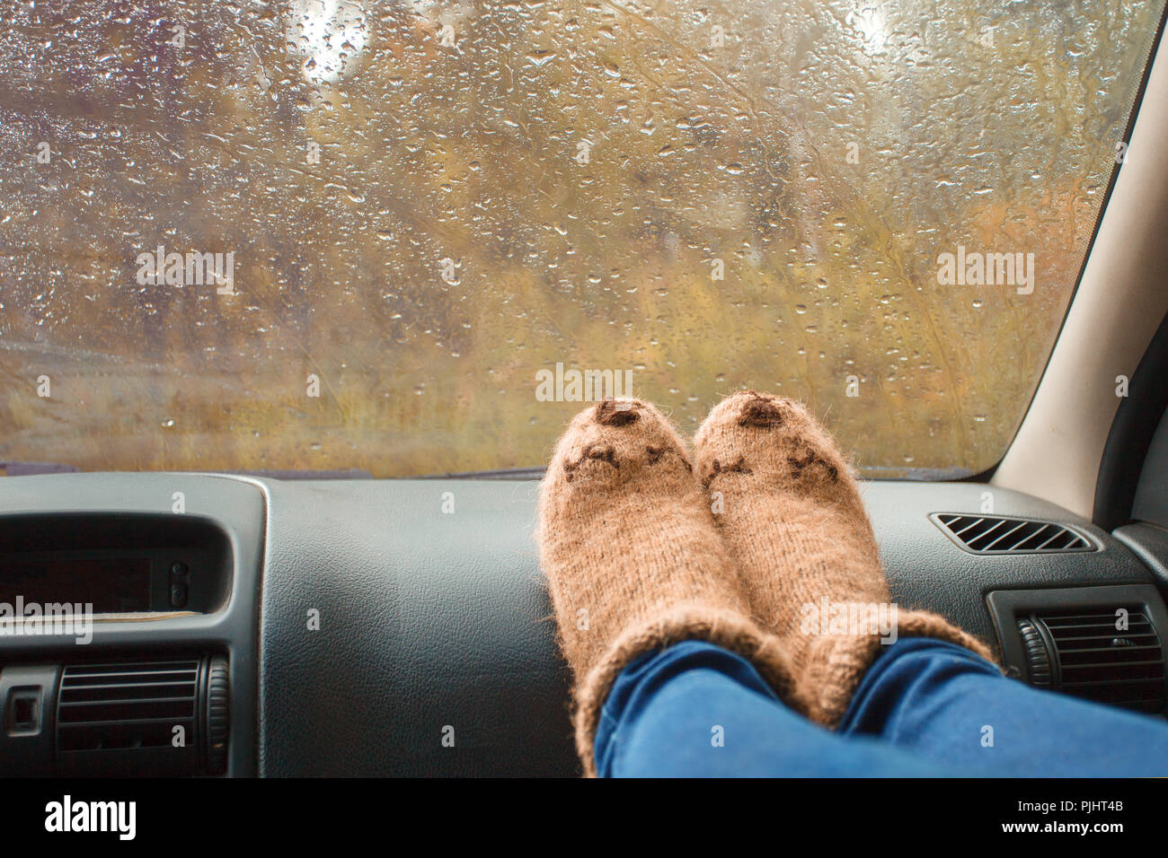 Woman legs in warm cute socks on car dashboard. Drinking warm tee on the way. Fall trip. Rain drops on windshield. Freedom travel concept. Autumn week - Stock Image