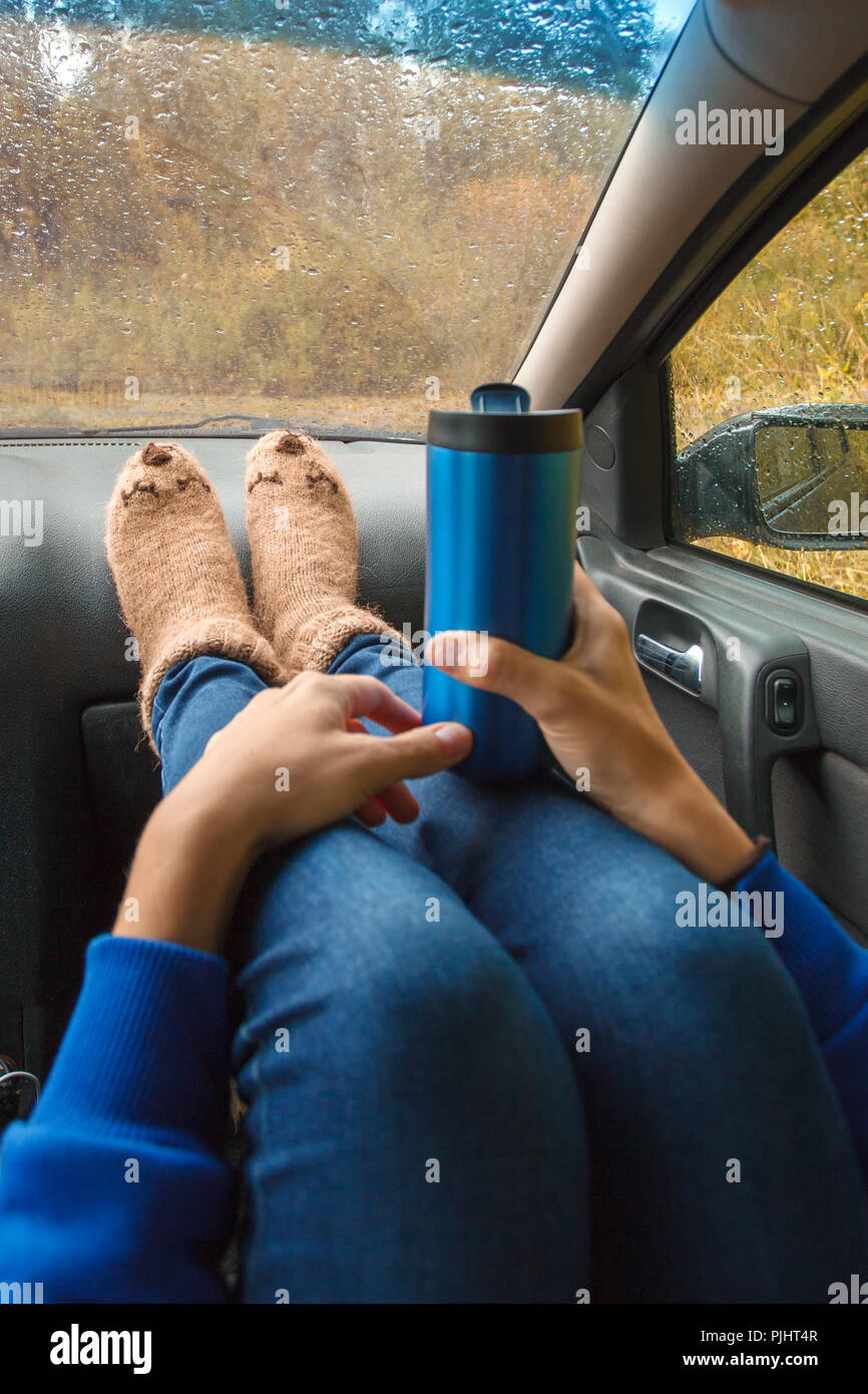 Feet in warm cute socks on car dashboard. Travel, road trip and autumn fall concept. Focus on thermos bottle cup with hot drink in female hands. - Stock Image