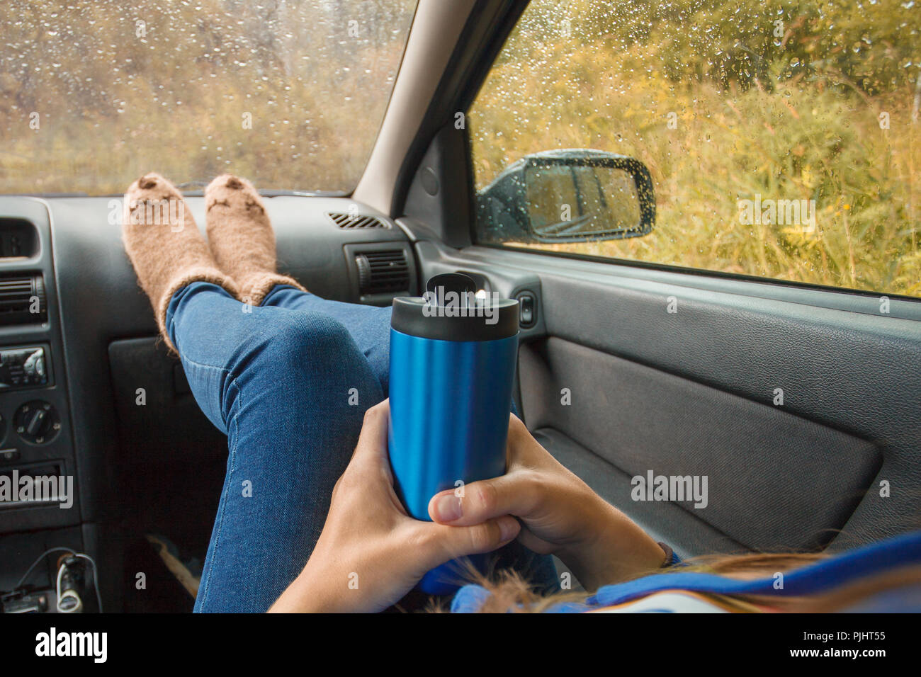 Feet in warm cute socks on car dashboard. Travel, road trip and autumn fall concept. Focus on thermos bottle cup with hot drink in female hands. Autum - Stock Image