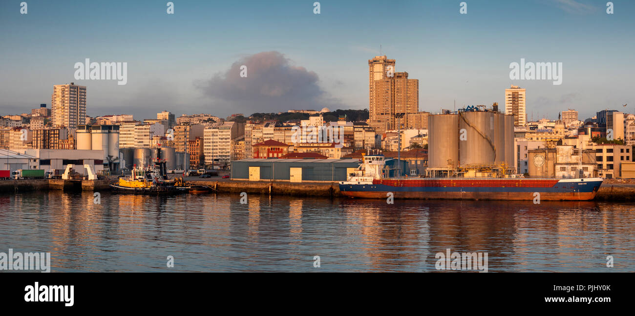 Spain, Galicia, A Coruna, harbour, waterfront at sunset, Eems Exe oil tanker at quay panoramic - Stock Image