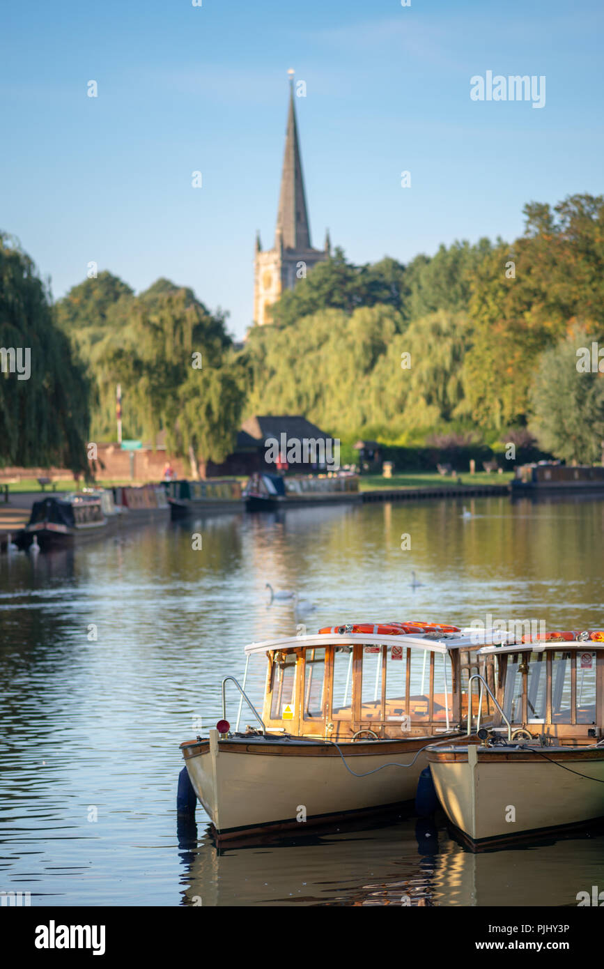 wooden edwardian boats moored up together in a typical English river scene in early autumn or fall with church in background - Stock Image