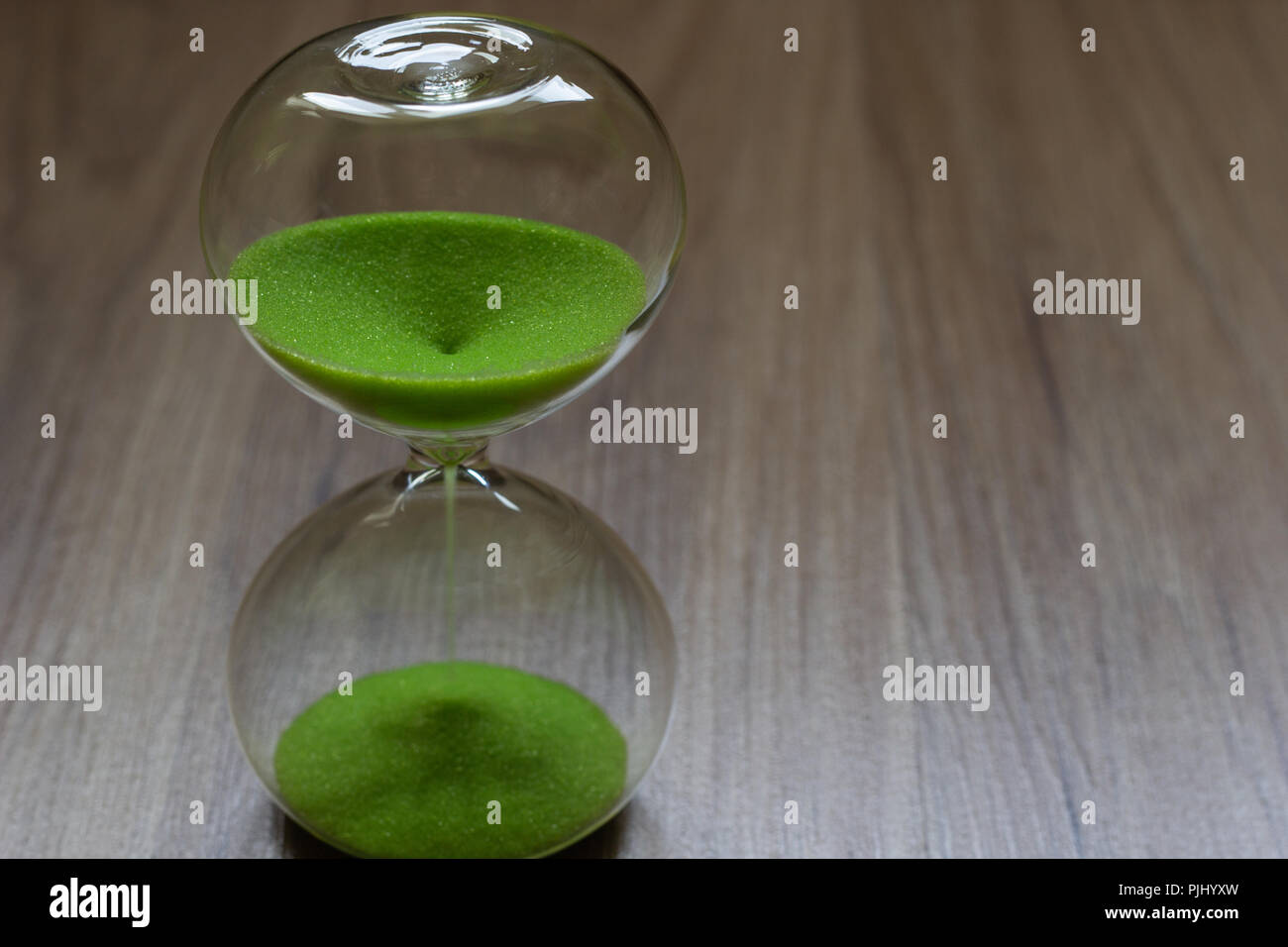 Hourglass with green sand, life time passing concept Stock Photo