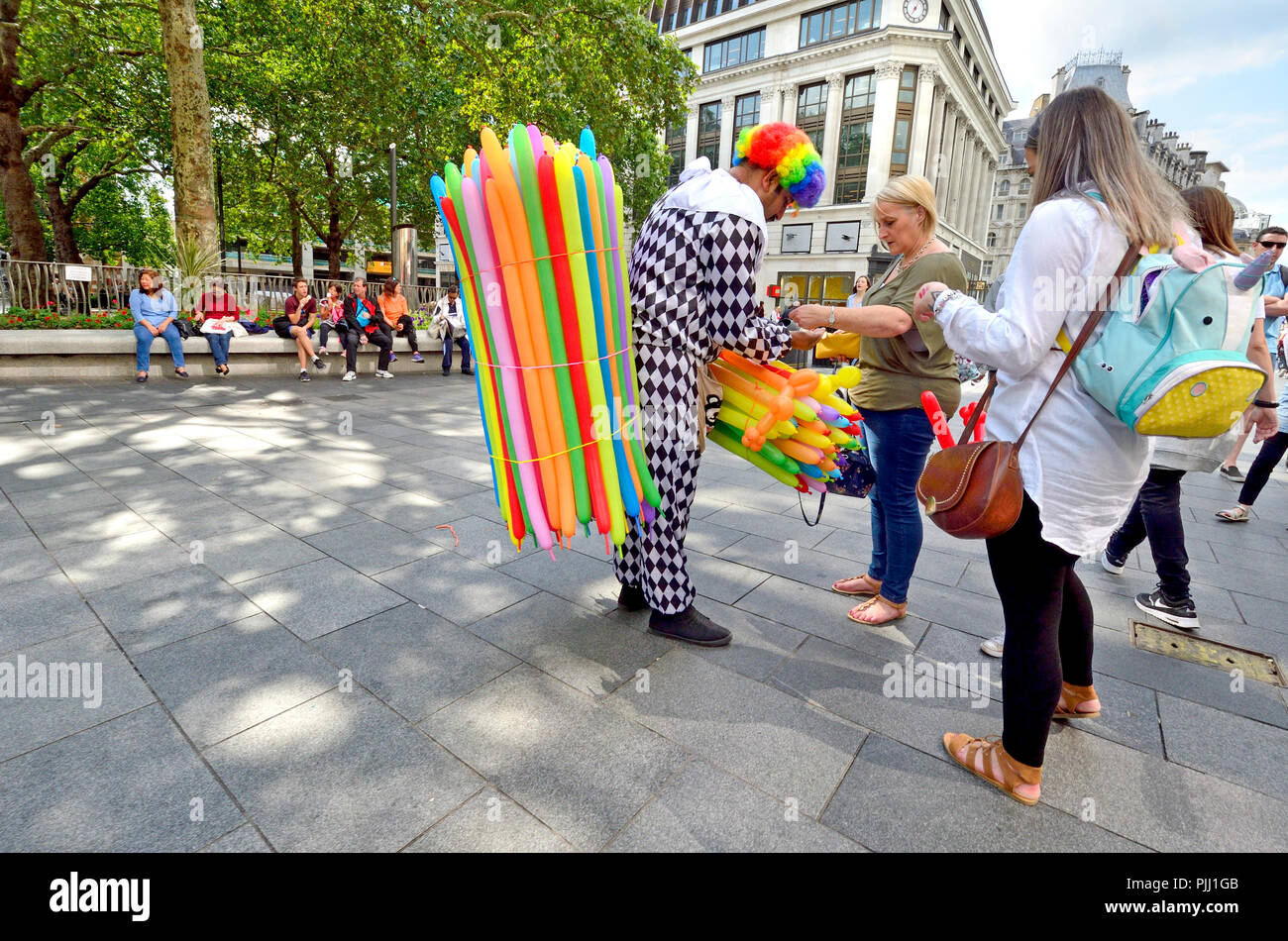 Clown selling balloon animals in Leicester Square, London, England, UK. - Stock Image