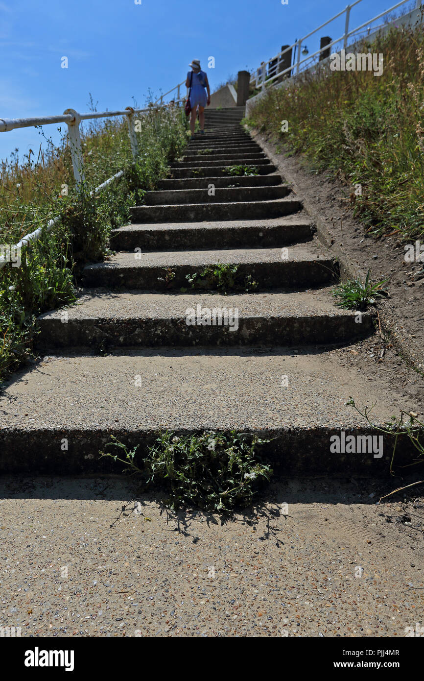A woman wearing summer clothing climbs a steep flight of concrete steps bordered by a handrail on a sunny day with a bright blue sky. - Stock Image