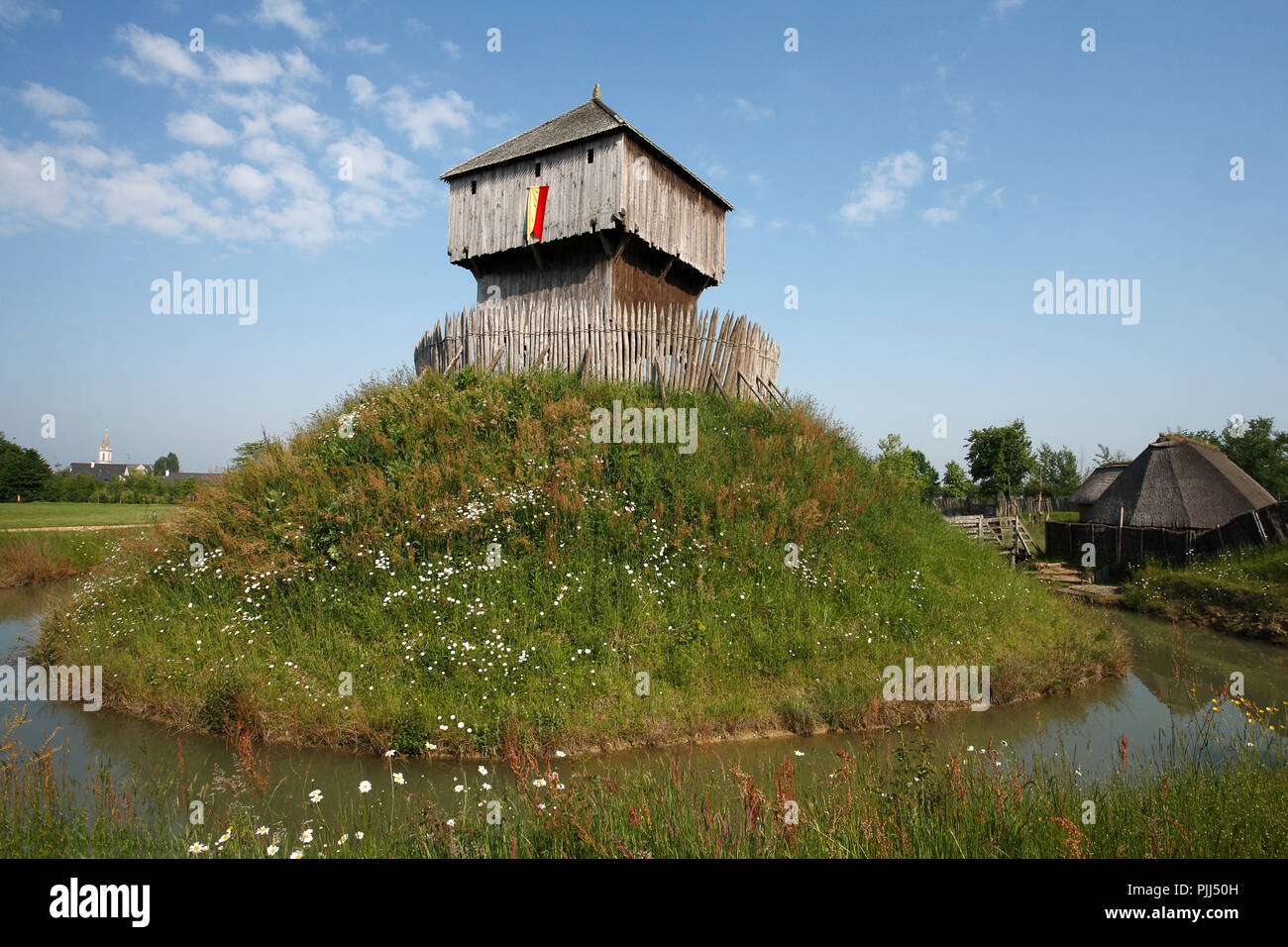 France, Saint Sylvain d'Anjou motte-and-bailey castle with moats and village. Historical reconstruction - Stock Image
