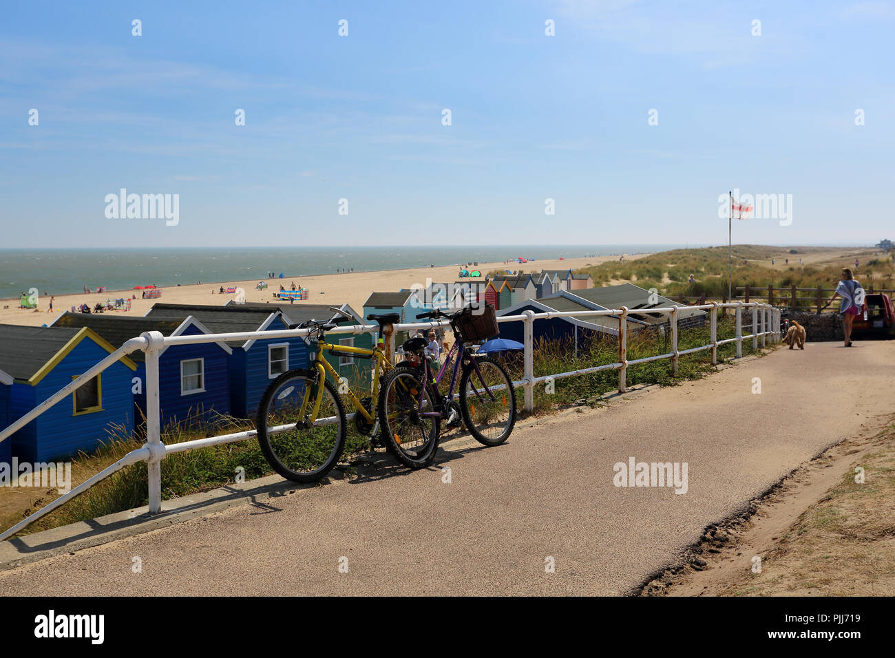 Bicycles secured to railings next to the beach at Gun Hill, Southwold, Suffolk, UK - Stock Image