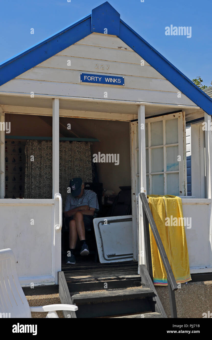 An elderly man snoozes inside his beach hut at Southwold, Suffolk, UK, which is, ironically, called '40 Winks' - Stock Image