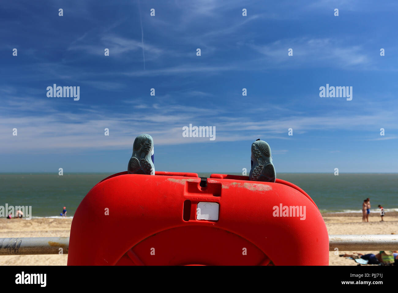 Found property in the form of a pair of children's shoes placed on top of a lifebelt at Southwold, Suffolk, UK. - Stock Image