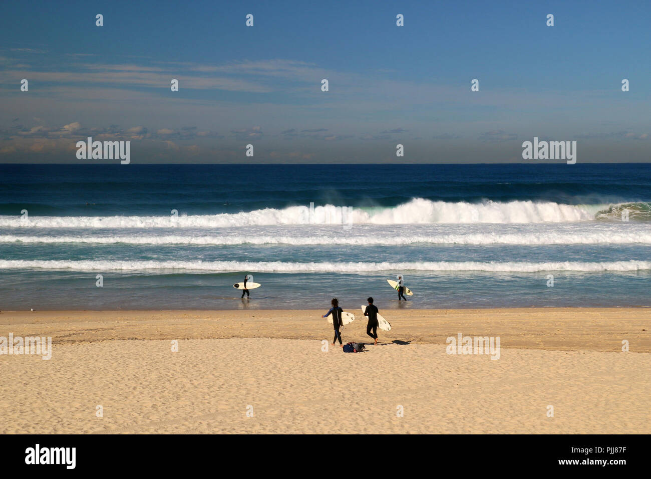 Deep blue Pacific ocean beach scene with huge waves and surfers walking on the beach and surfing, Bondi beach in Sydney, Australia - Stock Image