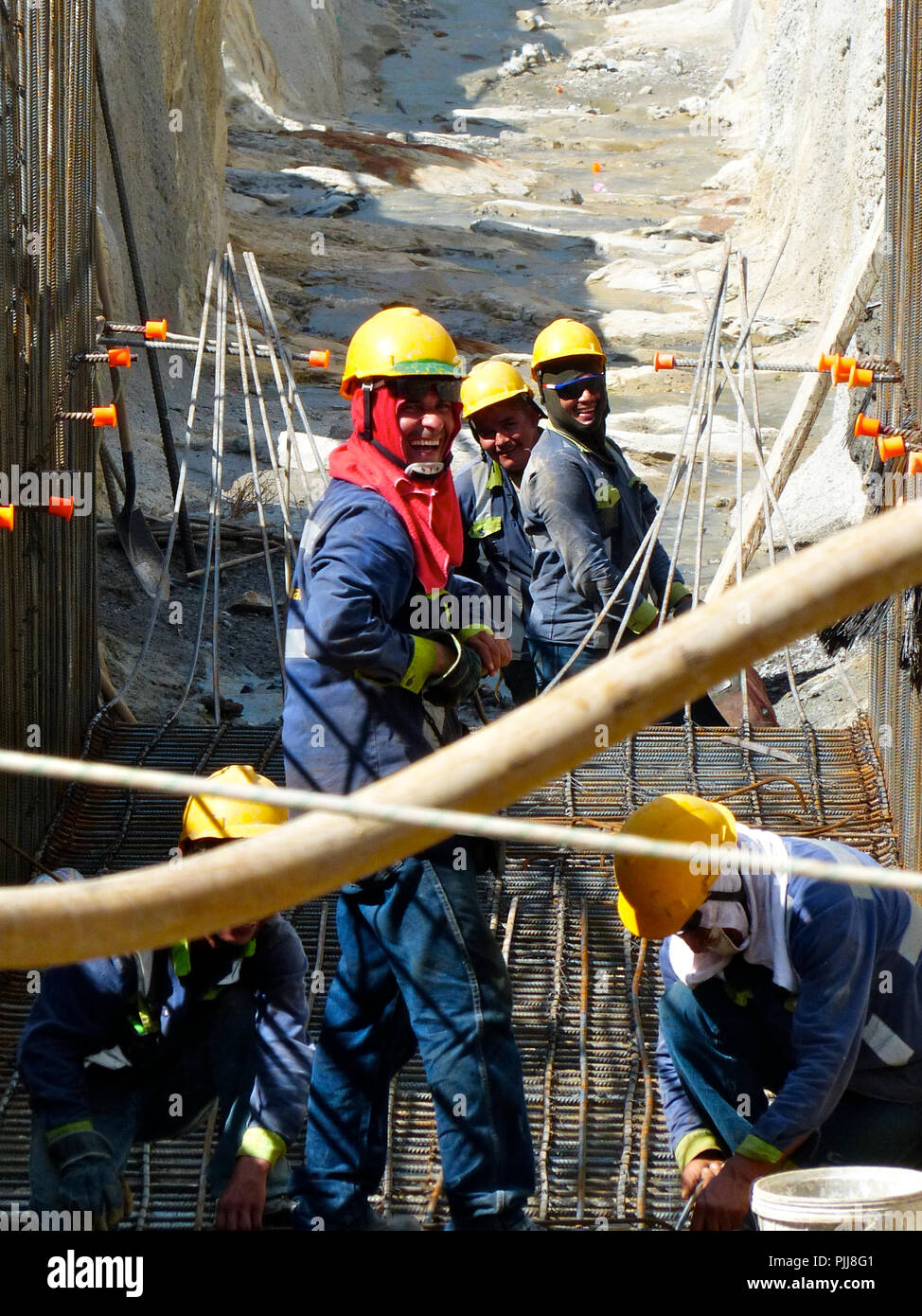 a group of five welders building the mesh for a concrete reinforcement in a hydropower Project wearing safety helmets and smiling - Stock Image