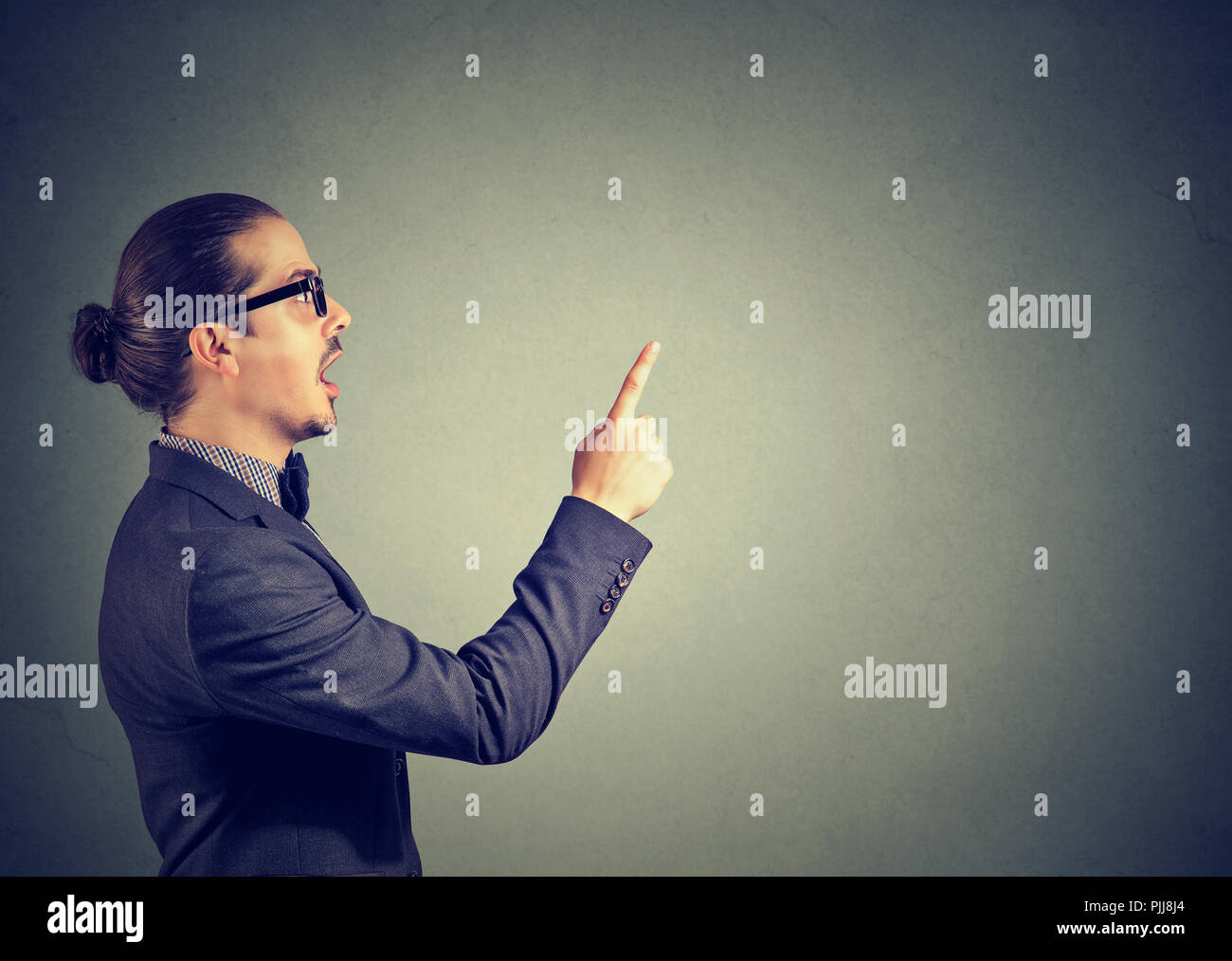 Side view of business man in holding finger up having bright idea on gray background - Stock Image