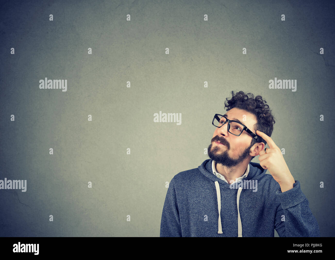 Adult handsome man thinking looking away in inspiration while creating new plan and daydreaming - Stock Image