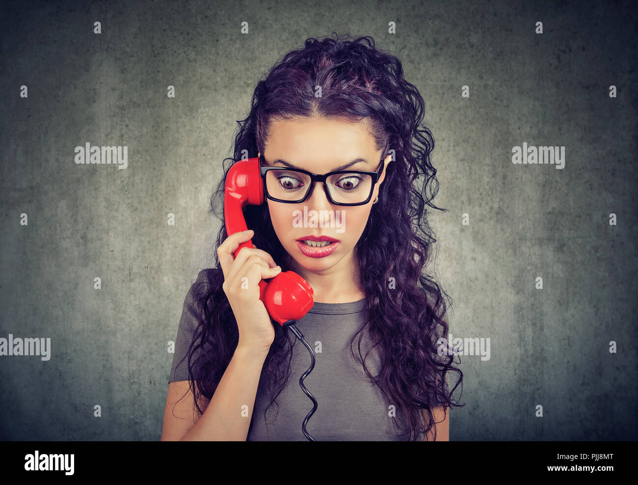 Woman receiving shocking news on a phone and looking down with fear. - Stock Image