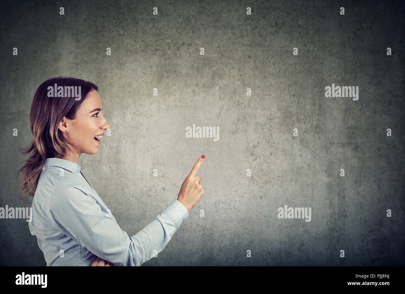 Side view of excited woman holding finger up having bright idea on gray background - Stock Image