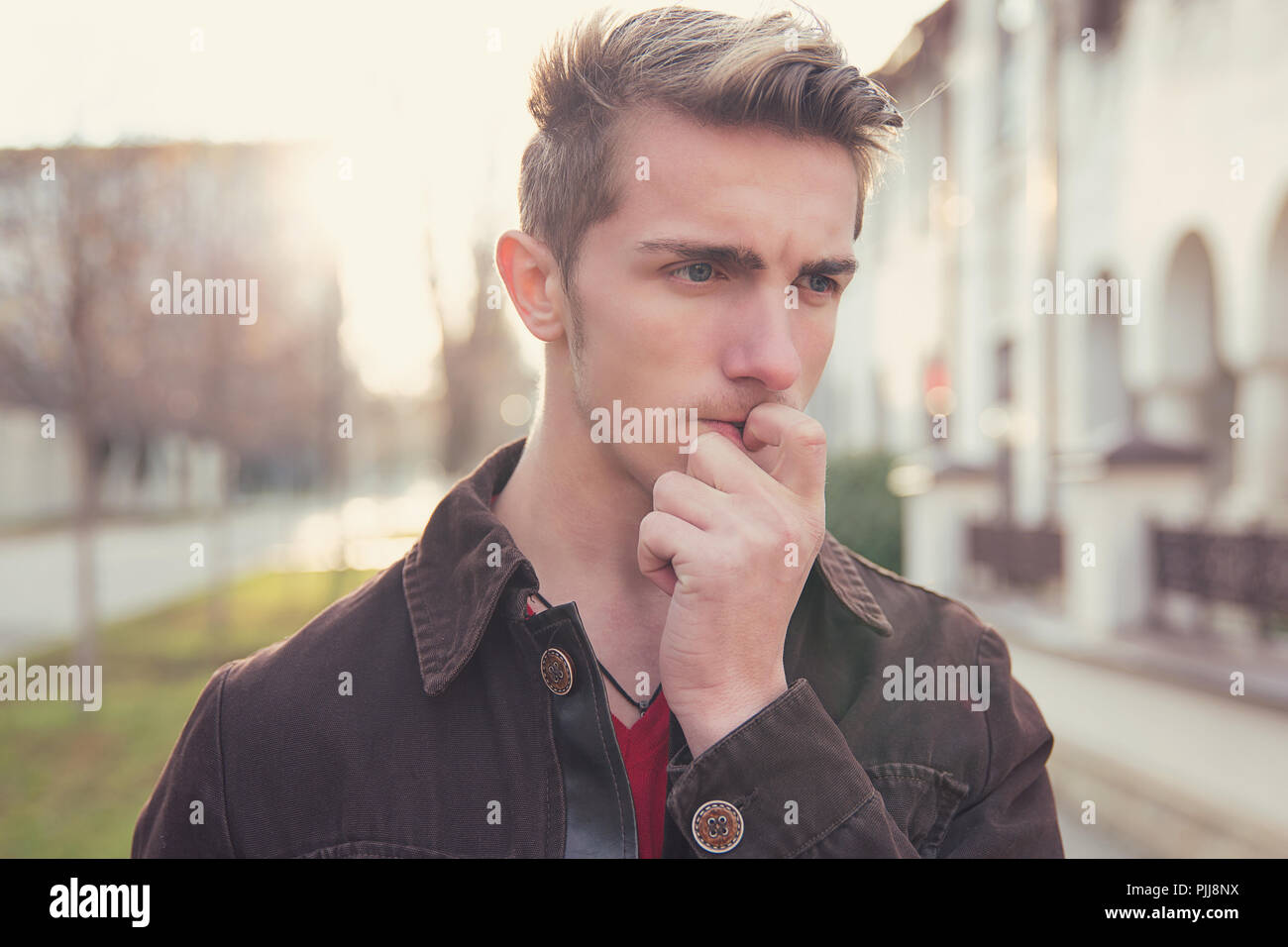 Young preoccupied man in doubts biting nails and looking away while standing on street - Stock Image
