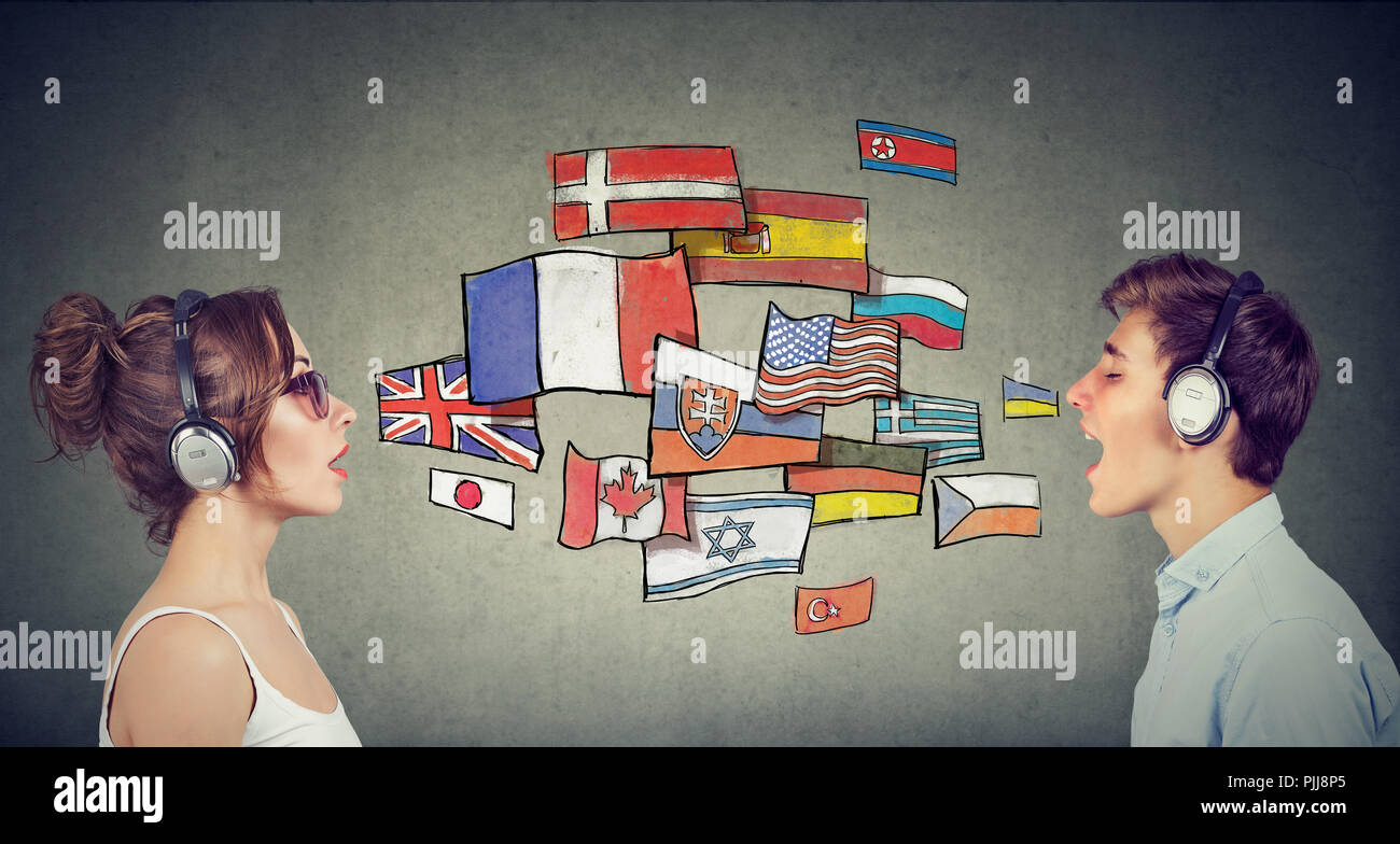 Young woman and man in headphones learning different languages communicating through simultaneous interpretation - Stock Image