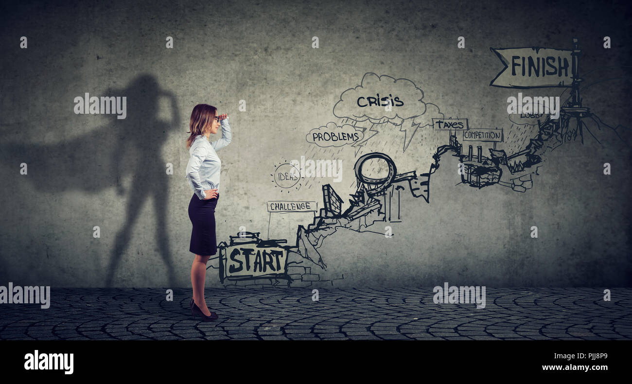 Business career challenges concept. Businesswoman imagining to be a super hero looking aspired making career plans - Stock Image