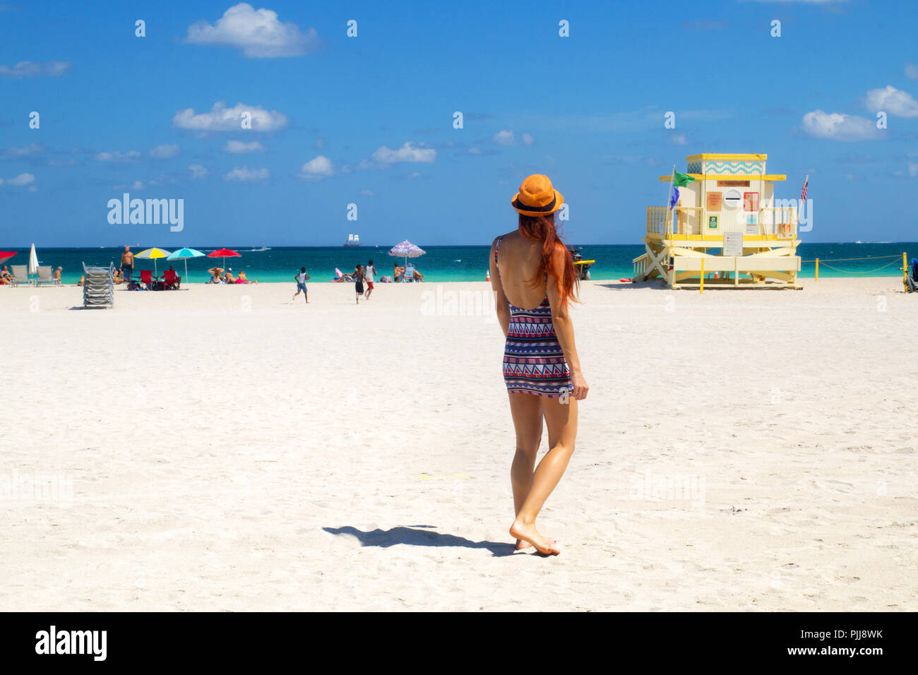 Miami Beach Florida, Hallouver park, attractive woman in mini dress walking towards Atlantic ocean Miami beach, rescue lifeguard art deco tower - Stock Image