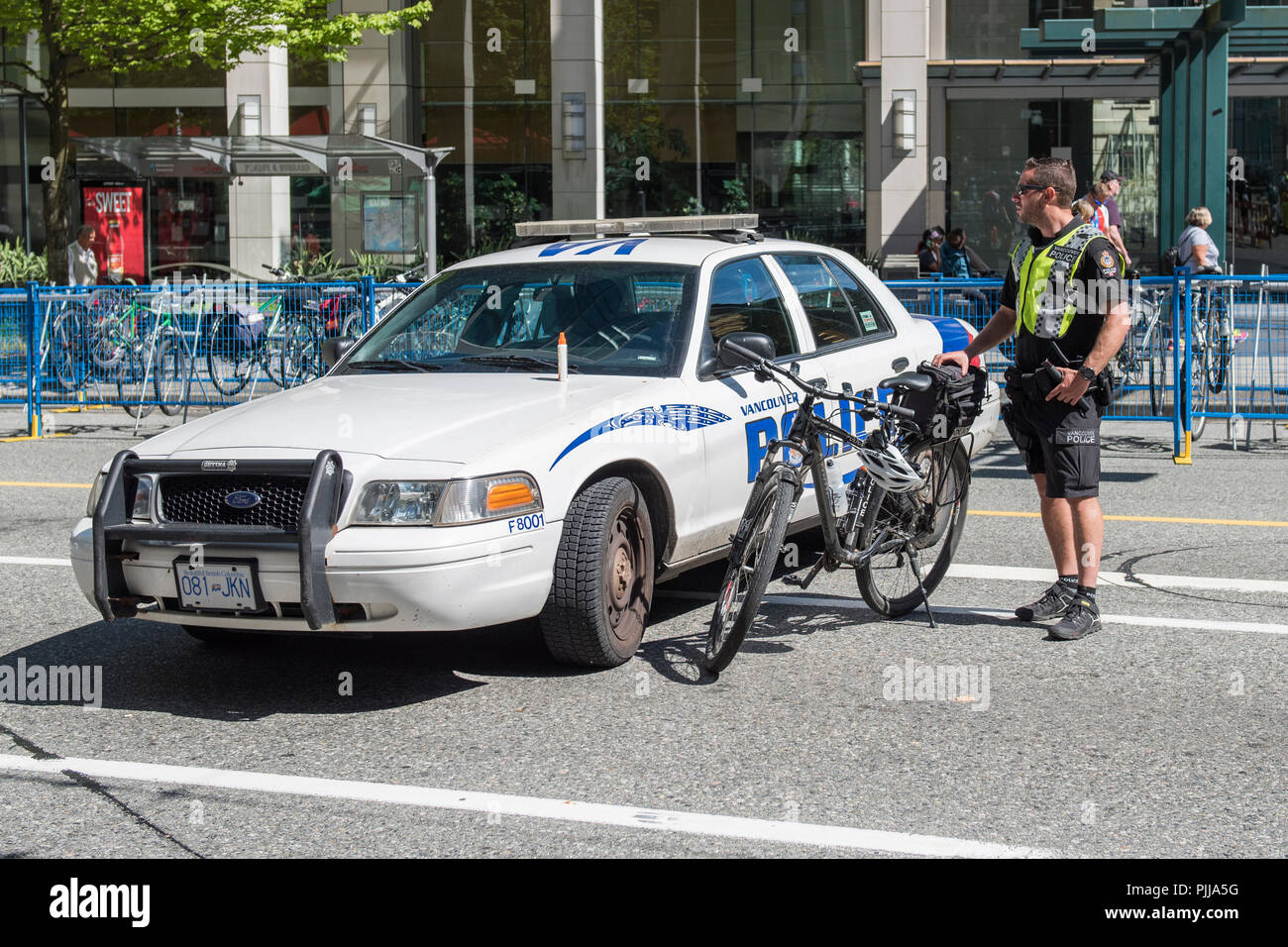 Vancouver City Policeman with bike, and vehicle blocking the street during an event, Vancouver city. - Stock Image