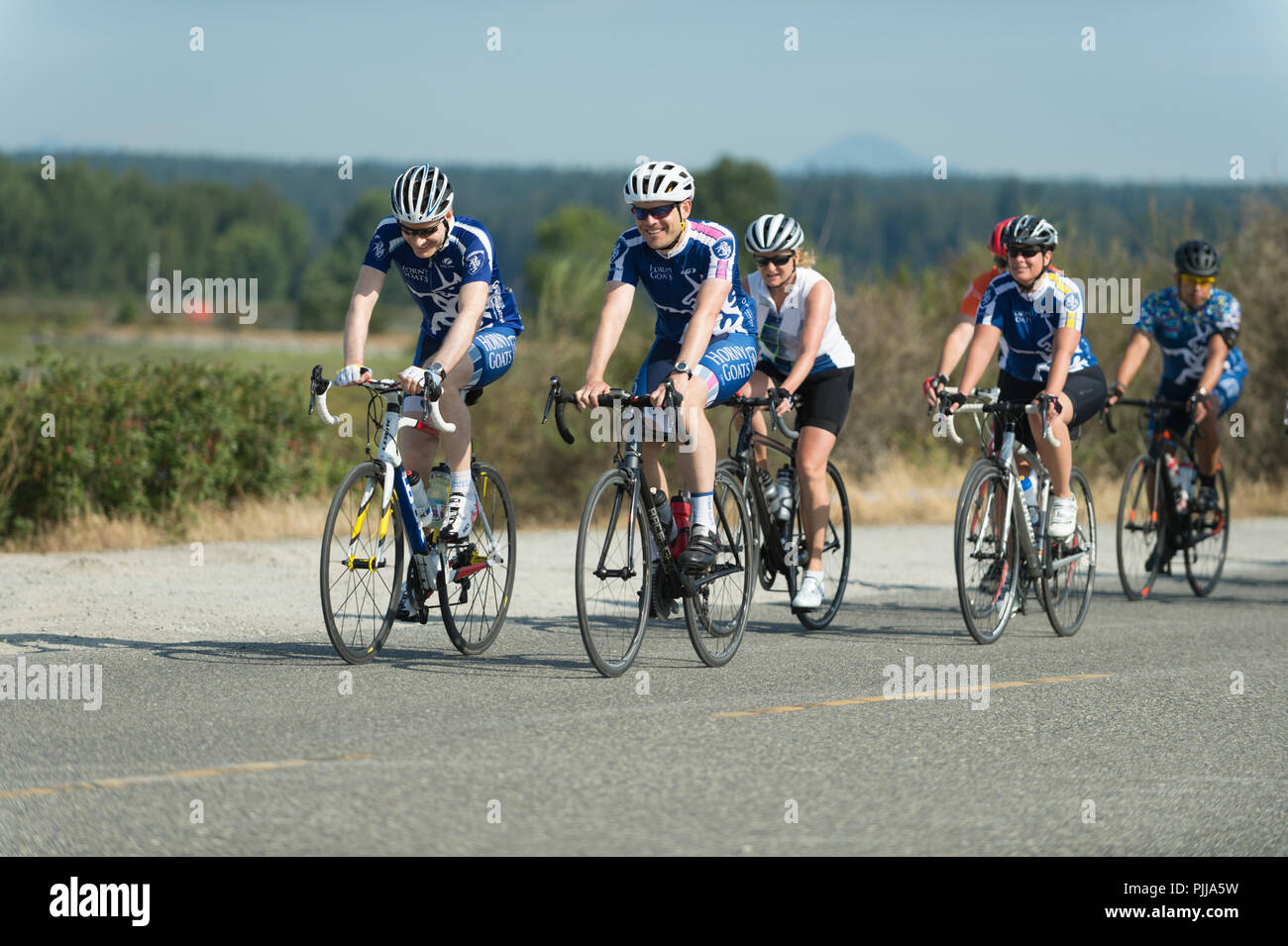 Bicyclists wearing helmets, cycling down a roadway. - Stock Image