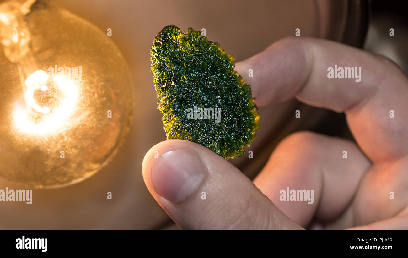Moldavite. Green mineral of meteoritic origin. Close-up of rare tektite. Vitreous silica rock of raw rough surface in human hand. Collector's piece. - Stock Image