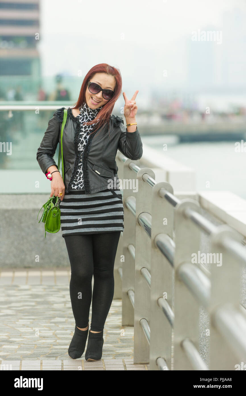 Beautiful Asian woman smiling giving peace sign to camera. Hong Kong, China. - Stock Image