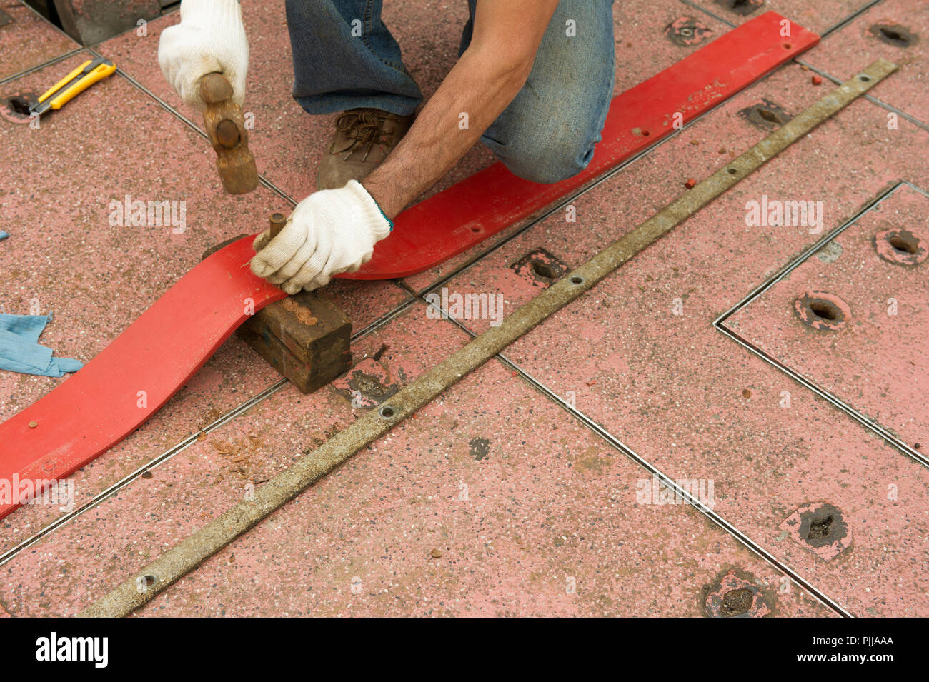 Worker wearing gloves, punching holes in leather strap, with hammer and punch tool. - Stock Image