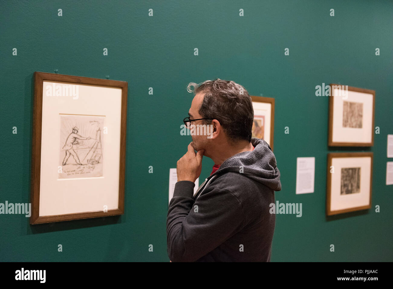 Male art lover, gazing at artwork on a wall. - Stock Image