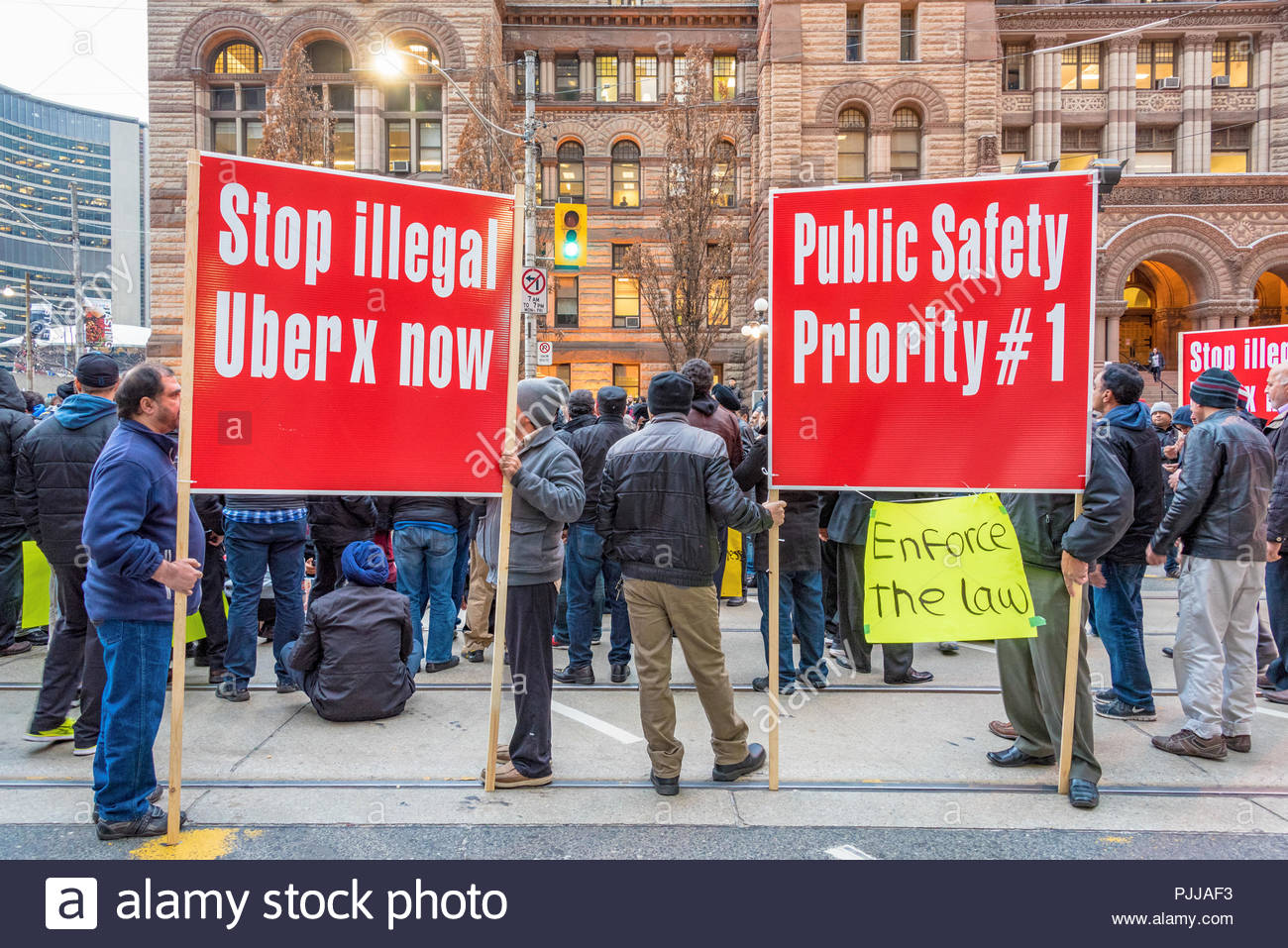 Toronto taxi drivers protest against Uber X. They claim the city is not enforcing its bylaws. For hours, they blocked the intersection of Queen St. We Stock Photo