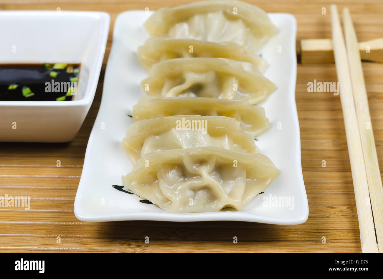 Steamed gyoza dumplings on white plate with soy souse. - Stock Image
