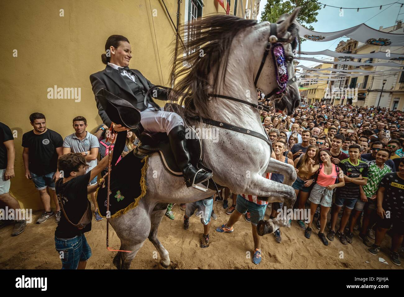 Mahon, Spain. 7 September, 2018:  A 'caixer' (horse rider) rears up on his horse in between the cheering crowd prior to the 'Jaleo' of the traditional Gracia Festival in Mahon, celebrating its patron, Our Lady of Grace Credit: Matthias Oesterle/Alamy Live News - Stock Image