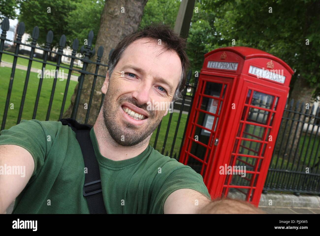 Tourist selfie with London phone box - red telephone kiosk in the UK. - Stock Image