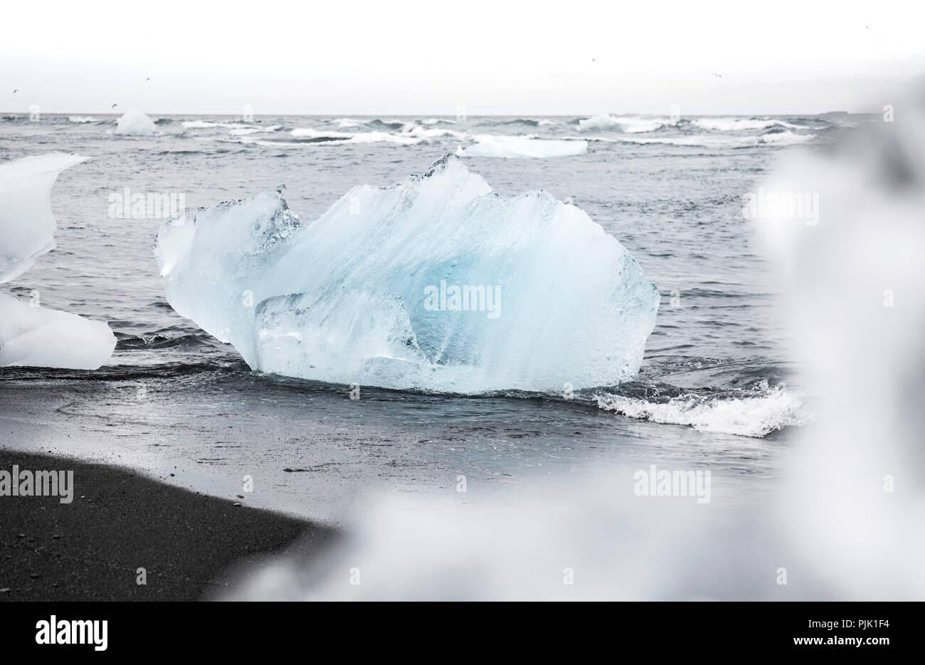 Ice block from the glacier on deep black sand in Jökulsárlón, Iceland - Stock Image